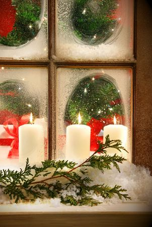 indoors: Frosted window looking into festive candles and holiday decorations