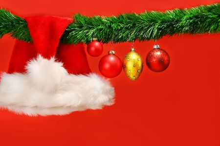 Green garland with santa hat and ornaments on red background photo