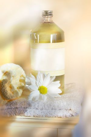 Bottle of linen water with towels and flower on cabinet photo