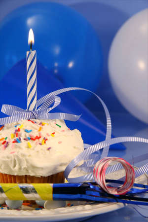 Festive decorations for small party cake with blue candle photo