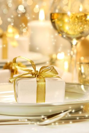 Little gold ribboned gift with gold background Imagens
