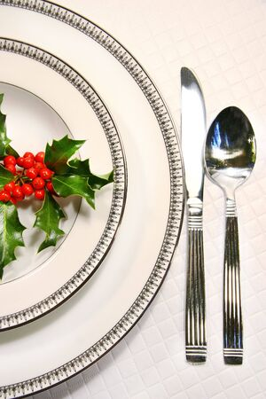 cater: Silver plate setting with a sprig of holly
