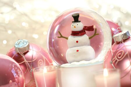 silver background: Snow globe with pink christmas balls and white lights in background Stock Photo