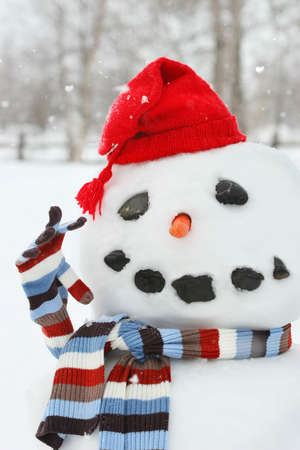 Building a snowman with red hat on a cold wintery day