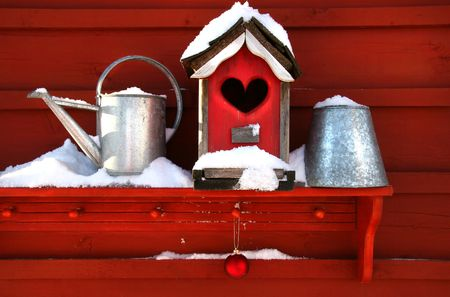 Old red birdhouse on shelf in the snow Stock Photo