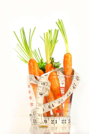 Carrots with water drops and a measuring tape wrapped around container photo