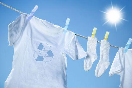 Eco-friendly wasgoed drogen op kleding lijn tegen een blauwe hemel met zon