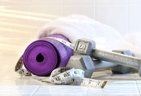Exercise mat with weights on white tile floor