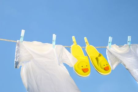 White t-shirts and slippers on the clothesline against a blue sky Stock Photo - 2639265