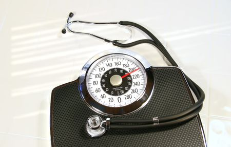 Weight scale with stethoscope on white tile photo