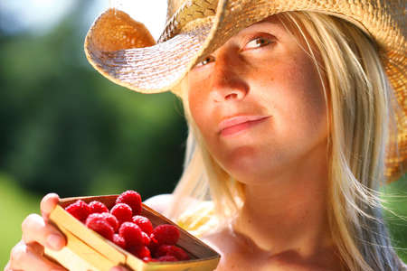 Woman showing a small basket of raspberries photo