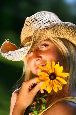 Young woman holding a big yellow daisy photo