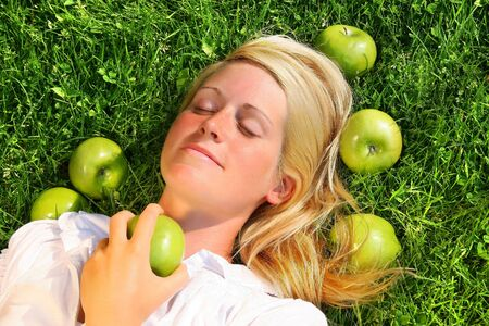 Young woman lying in the grass with green apples photo