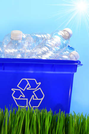 Bottles in recycling container bin in the grass photo