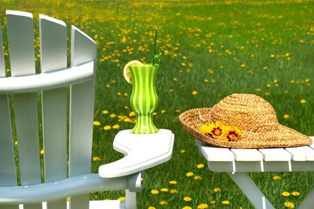 Adirondack chair on the grass with cool summer drink photo