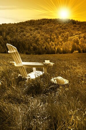 Relaxing on a summer chair in a field of tall grass at sunset photo