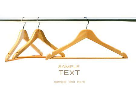Three coat hangers on a clothes rail photo