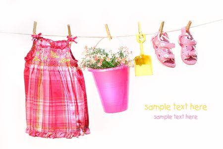 Little girl clothes and toys on a clothesline against white background Stock Photo