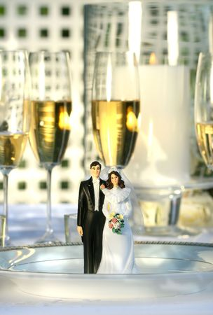 Wedding cake figurines on plate at dinner reception photo