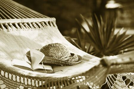 Hammock, book, hat, and glasses on a sunny summer day Sepia tone Reklamní fotografie