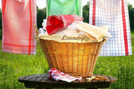 ropa colgada: Canasta de lavander�a en r�stica mesa con ropa