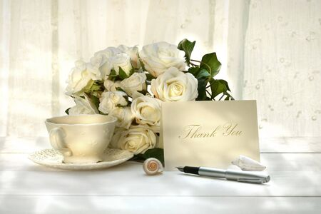 Writing invitation card with pen and a cup of tea photo
