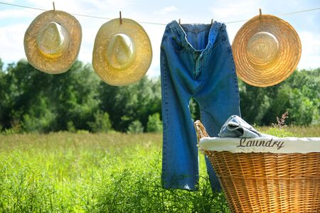 Blue jeans and straw hats on clothesline in a field