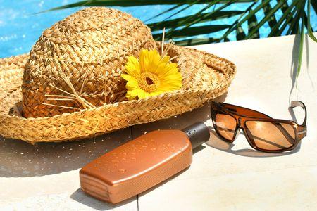 プールサイドの麦わら帽子、メガネ、日焼けローション 写真素材