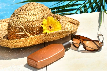 sunblock: Straw hat, glasses and suntan lotion by the pool
