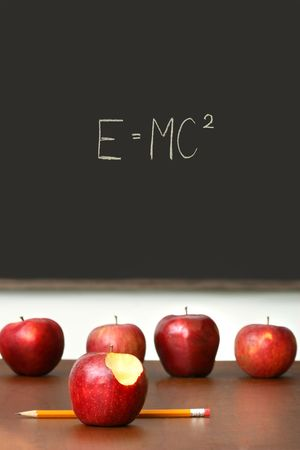 Apples on top of school desk with chalkboard in background photo