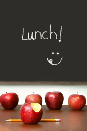 desk: Apples on top of school desk with chalkboard in background Stock Photo