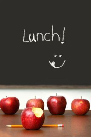 school desk: Apples on top of school desk with chalkboard in background Stock Photo