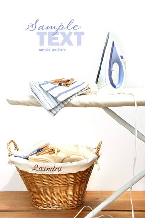 Ironing board with laundry against white background photo