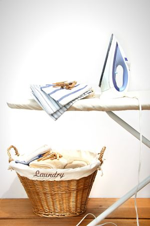 clothes pegs: Ironing board with laundry against white background