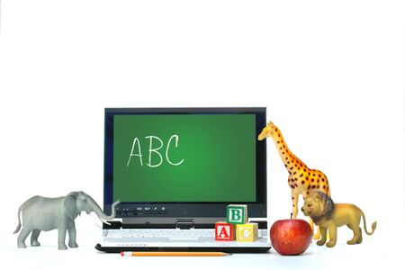 Laptop on desk with toy animals and apple on white photo