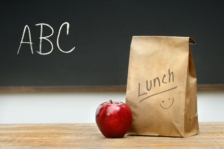 sack: Paper lunch bag on desk with apple