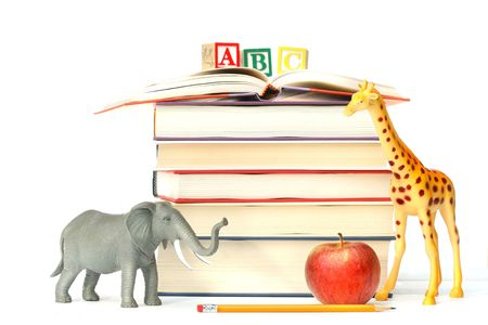Stack of books with toy animals and apple on white photo