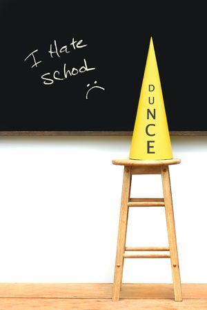 schoolroom: Yellow dunce hat on stool with chalkboard Stock Photo