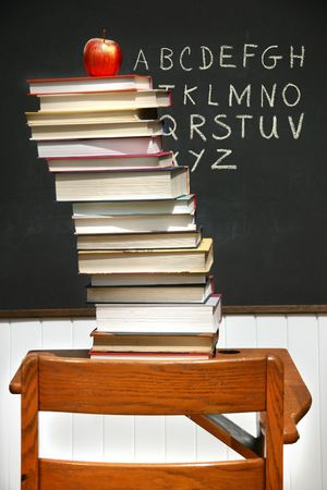 old desk: Stack of books on an old school desk with blackboard