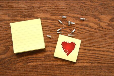 Yellow sticky note pads with silver push pins on oak wood photo