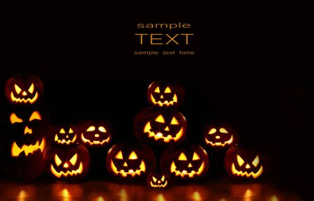 Lots of pumpkins lit brightly against a black  Stock Photo - 3621851