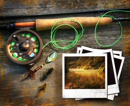 Fly fishing rod with pictures on wood background photo