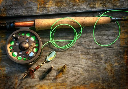 Fly fishing rod with polaroids pictures on wood background