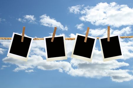 photos hanging on a rope with clothespins against blue sky Stock Photo - 3632696