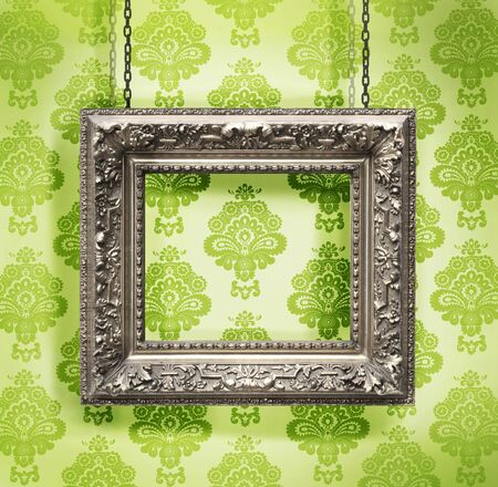 Silver picture frame hung against floral wallpaper background green photo