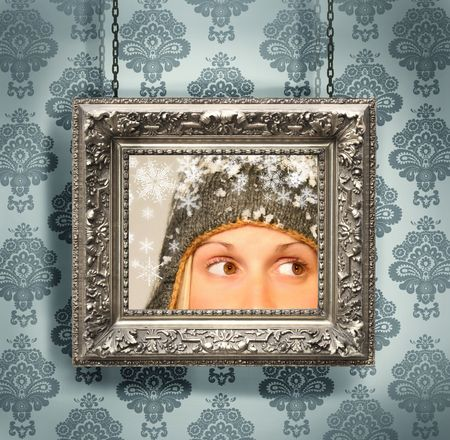 hung: Silver picture frame hung against floral wallpaper background blue Stock Photo