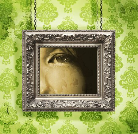 Silver picture frame hung against floral wallpaper background photo