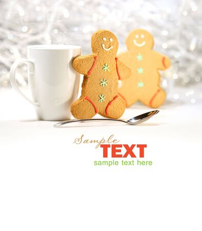 Hot holiday drink with gingerbread cookies on festive background photo