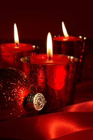 Red candles with ribbons against a background photo