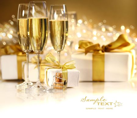 flutes: Glasses of champagne with gold ribbon gifts
